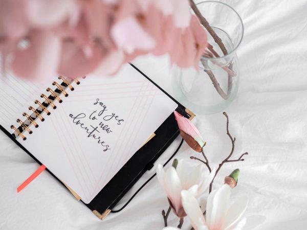 diario con fiori rosa. sul diario la scritta: say yes to new adventure